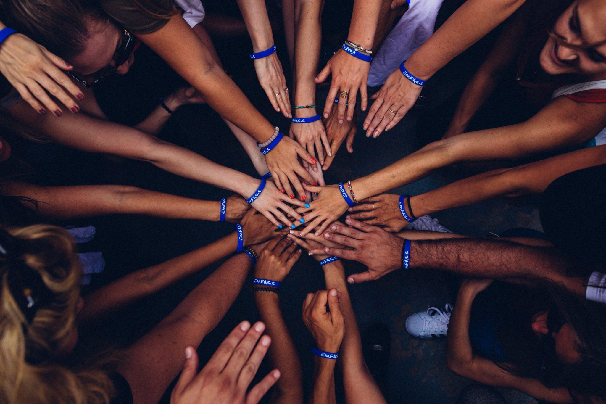Ungdomar i ring som håller sina händer in mot mitten av ringen