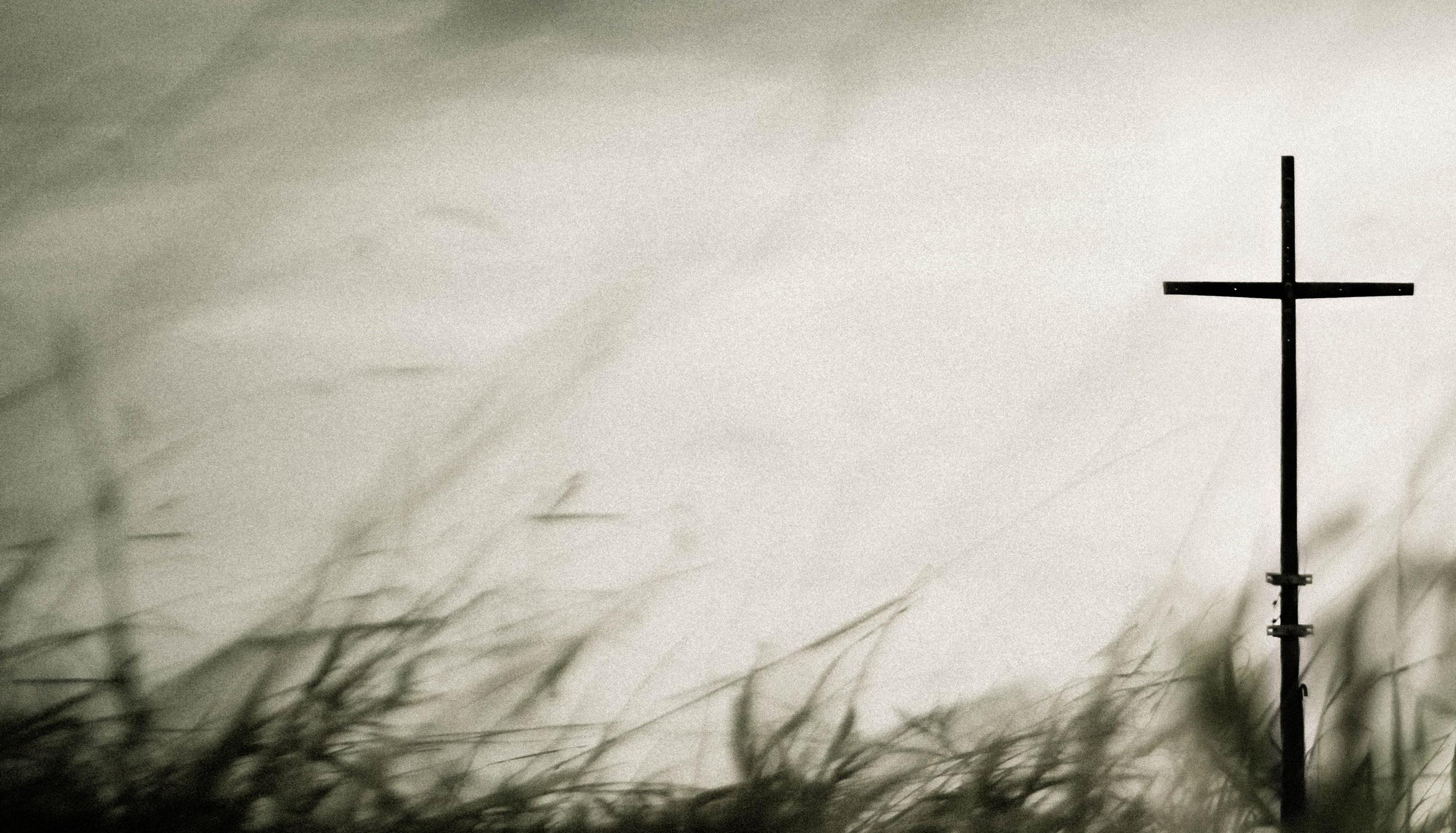 Kors med suddigt gräs i förgrunden