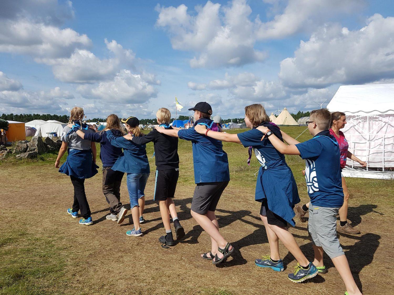 Scouter på led med händerna på varandras axlar