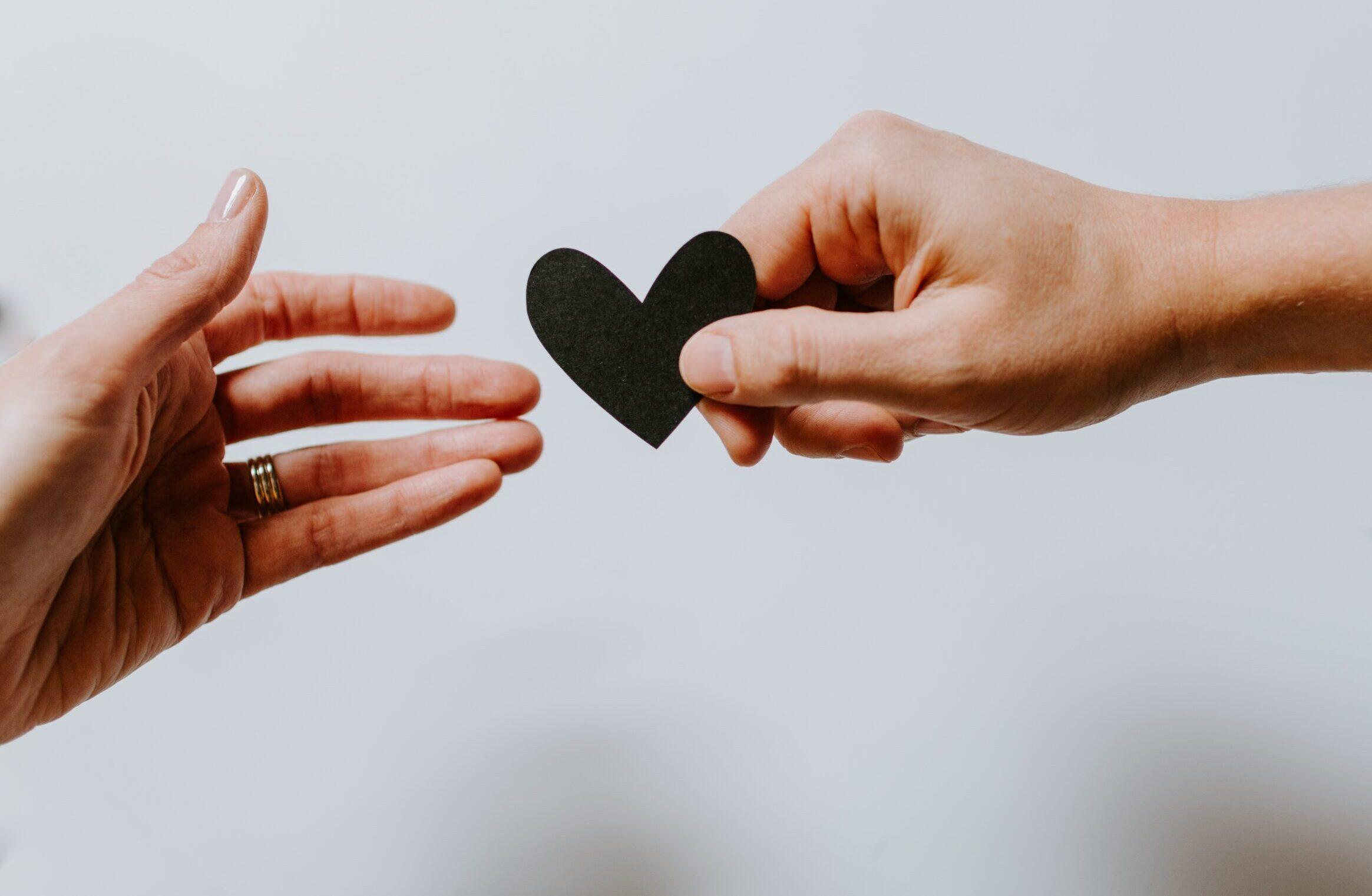 En hand ger en annan hand ett utklippt hjärta