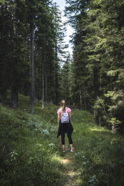 Kvinna går på stig i skogen