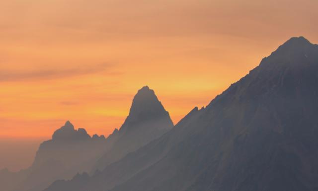 Bergstoppar i solnedgång