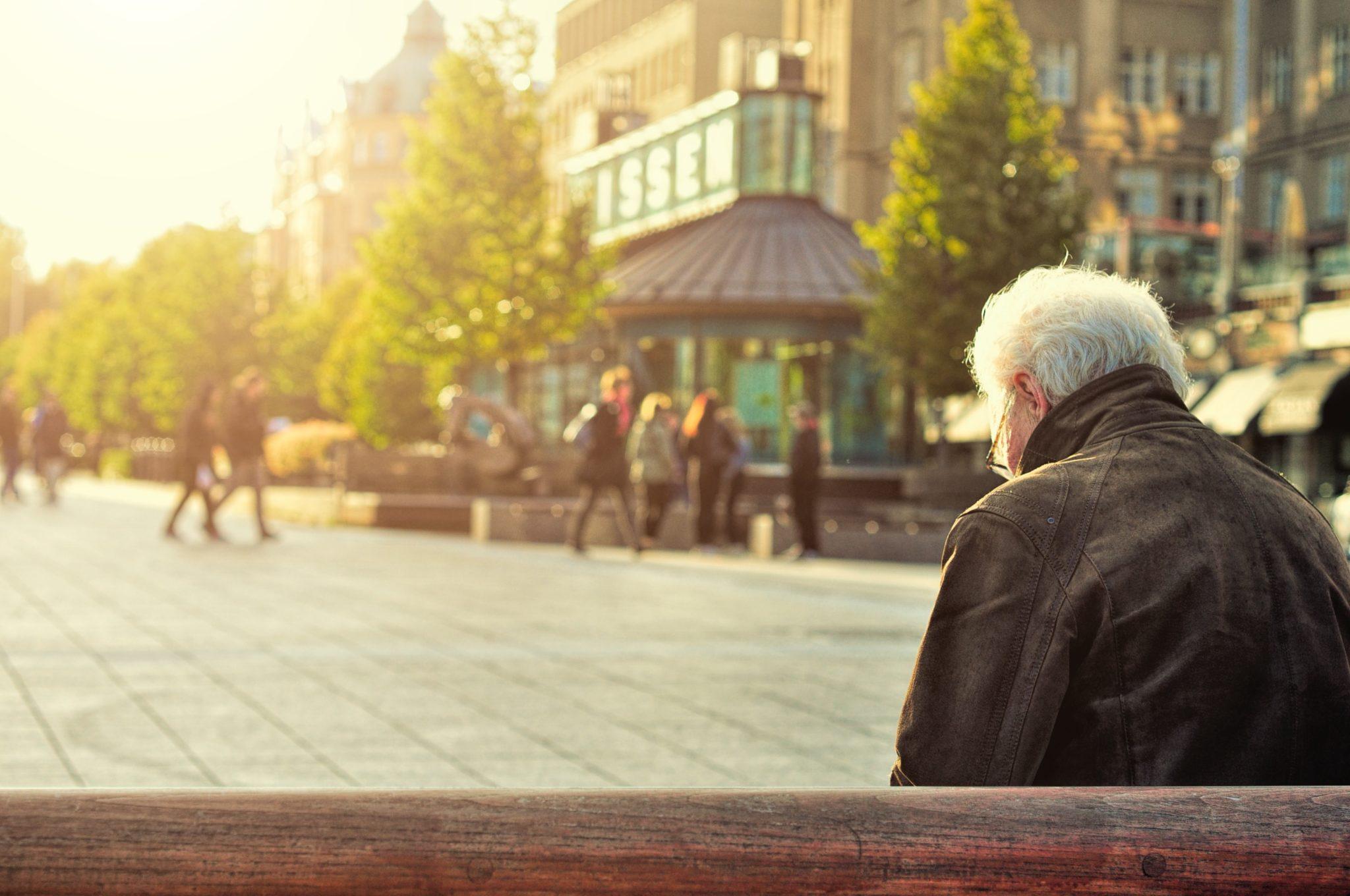 Ensam äldre man på parkbänk