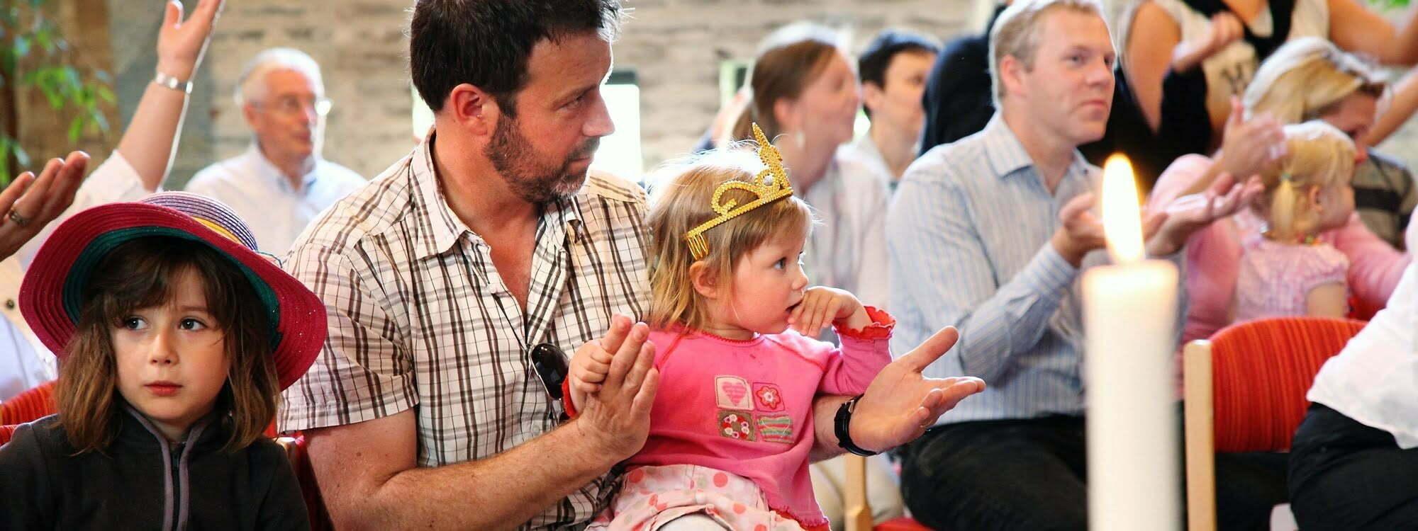 Foto på församling, flicka i pappas knä