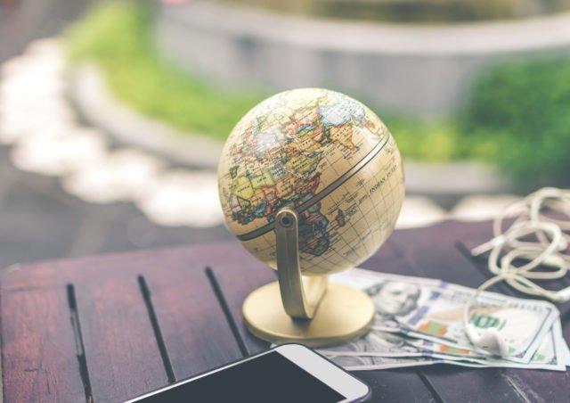 Jordglob, pengar och telefon på ett bord
