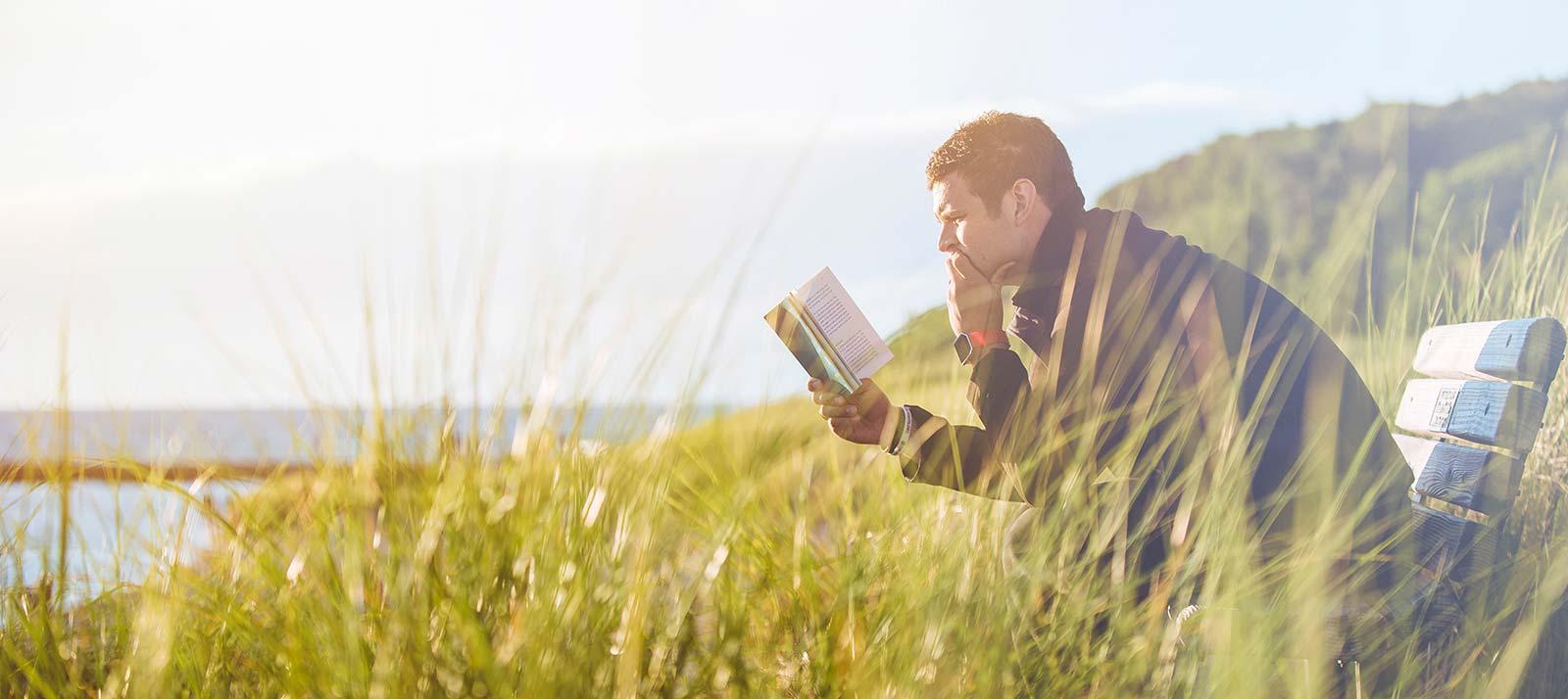 Man som läser bibeln ute i naturen