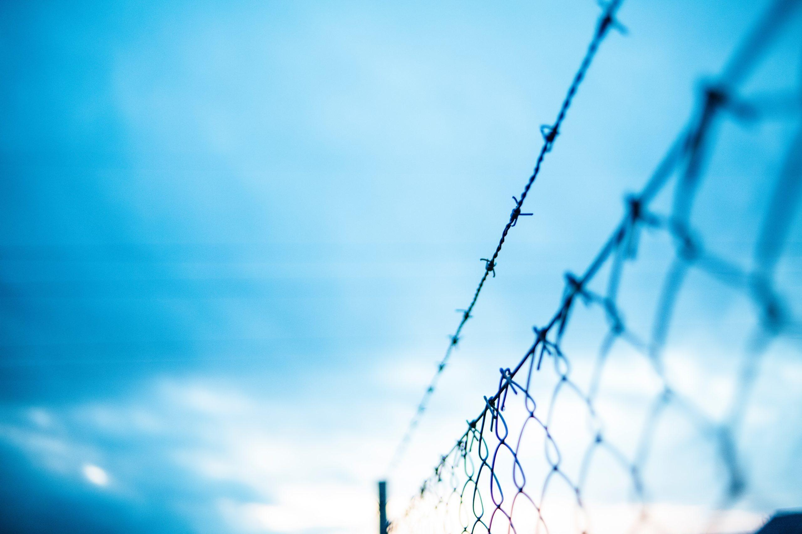Taggtrådsstängsel mot blå himmel