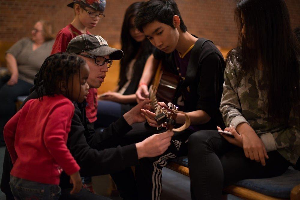 Unga man får hjälp att stämma sin gitarr