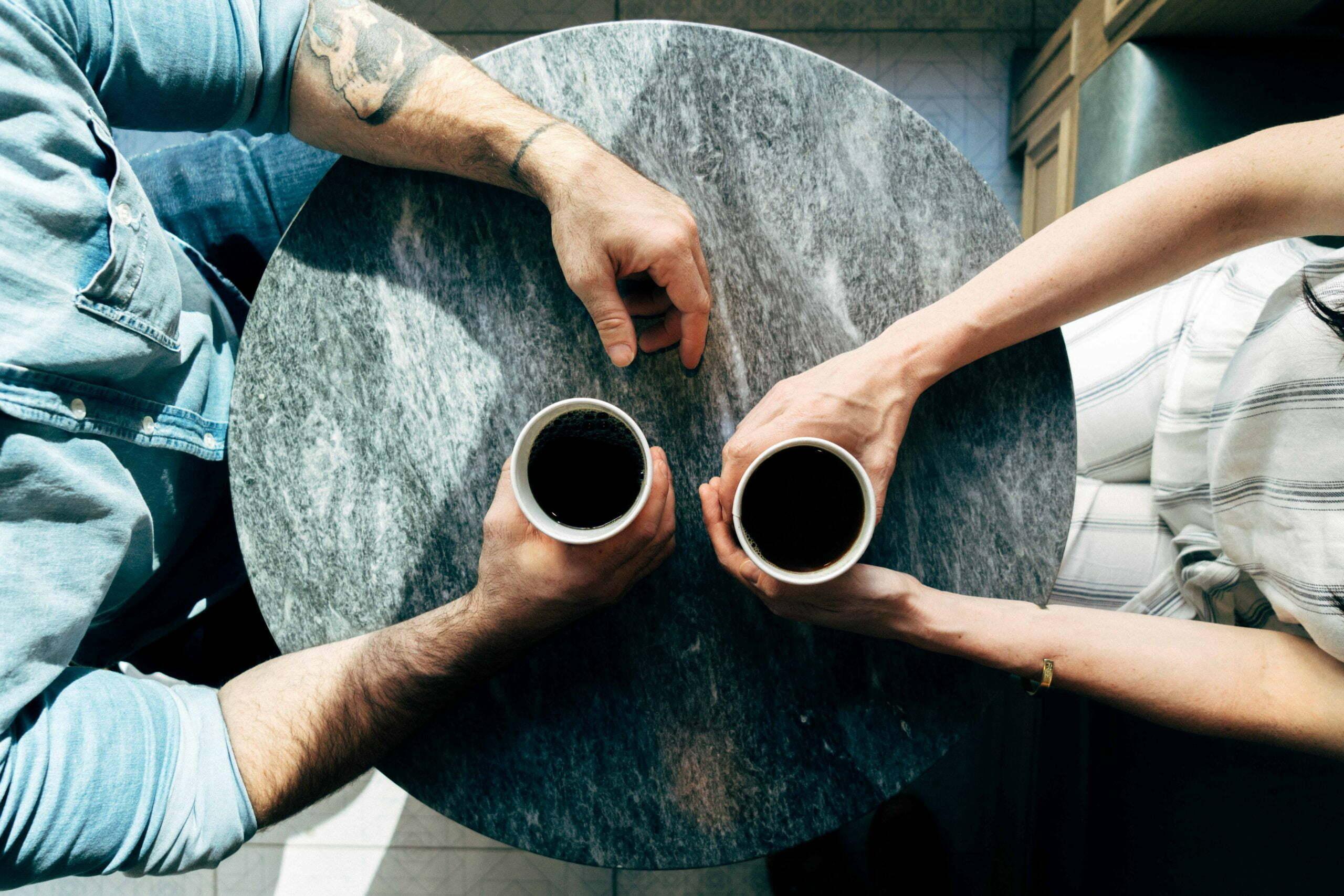 Två personer samtalar över var sin mugg med kaffe