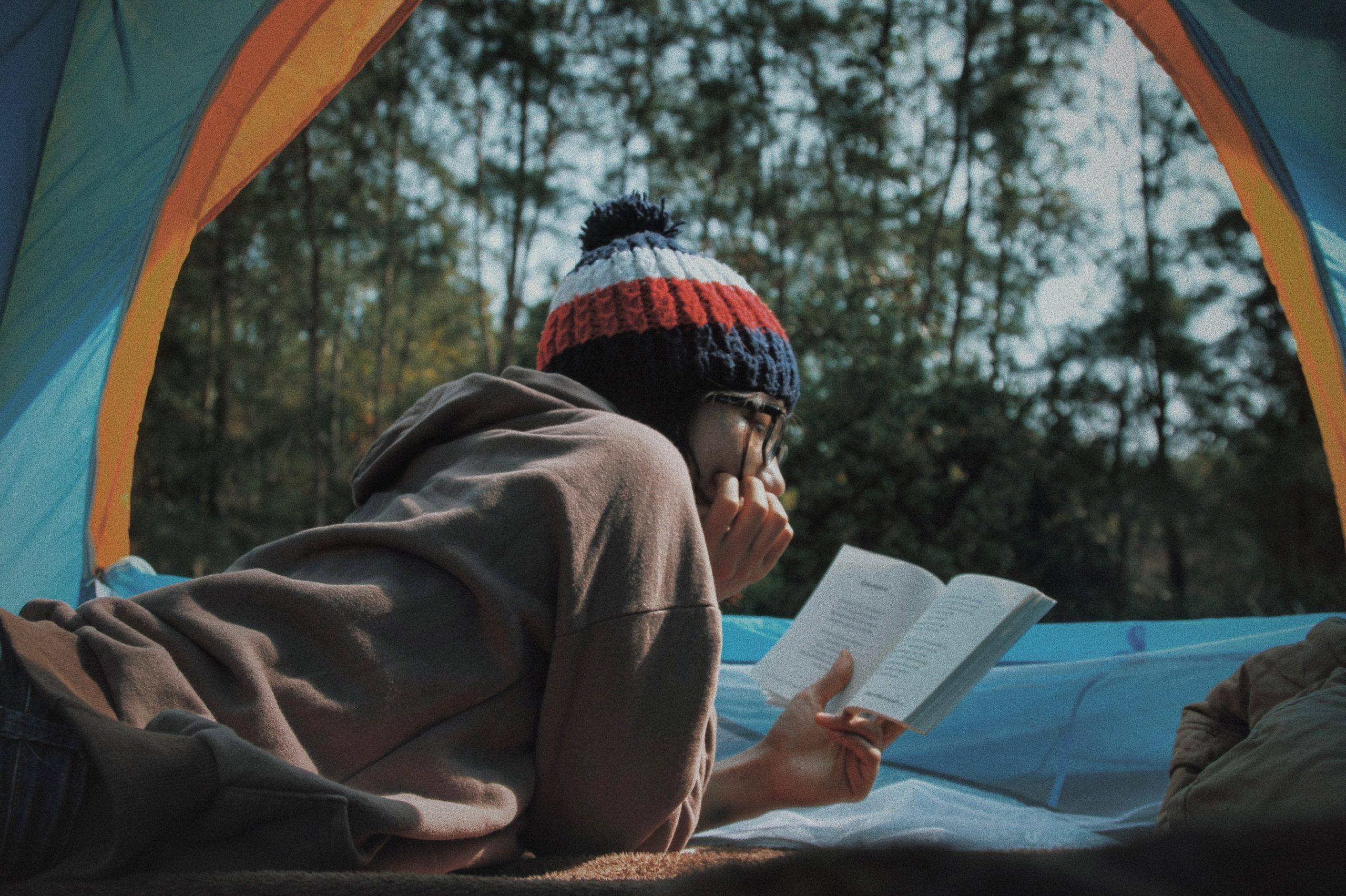 Ung kvinna ligger och läser en bok i ett tält