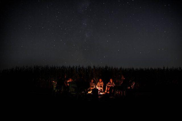 Stjärnklar natt med personer kring brasan