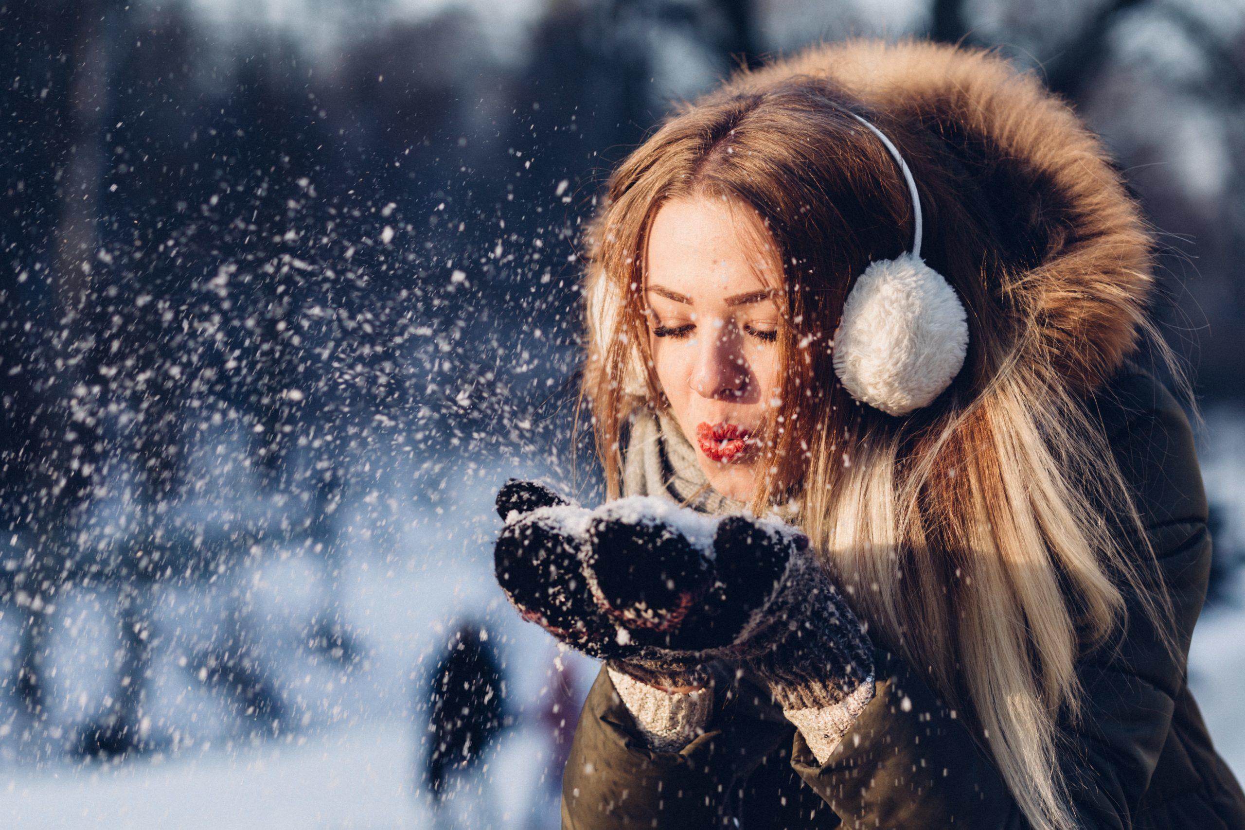 Tjej som blåsar snö från händerna