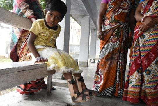 Barn med stöd kring fötterna