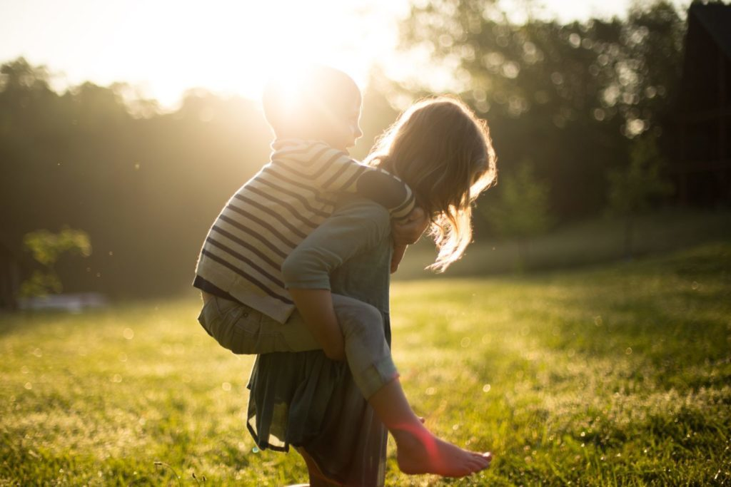 Ett barn som bär ett annat barn på ryggen