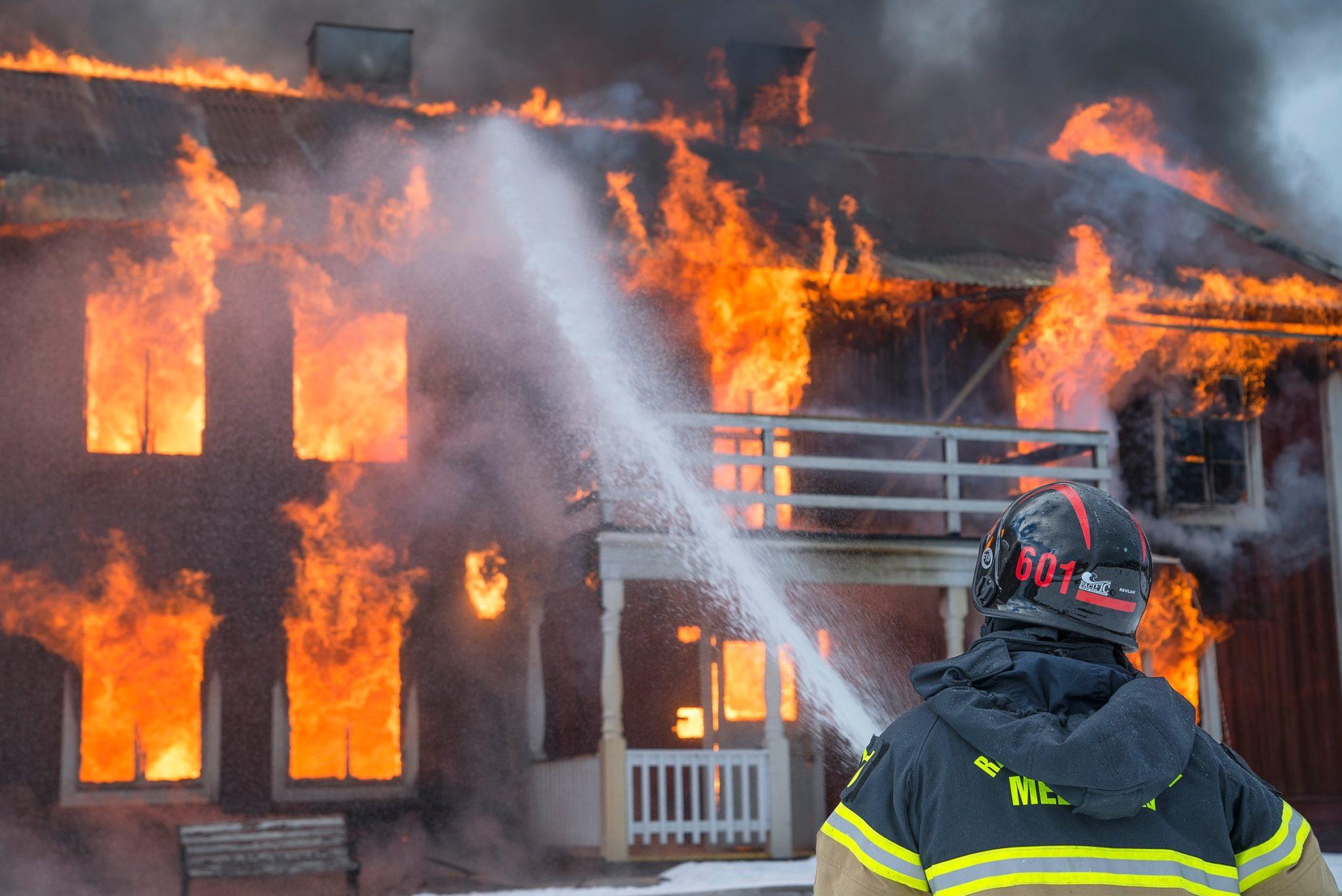 Brandman som sprutar vatten på brinnande hus
