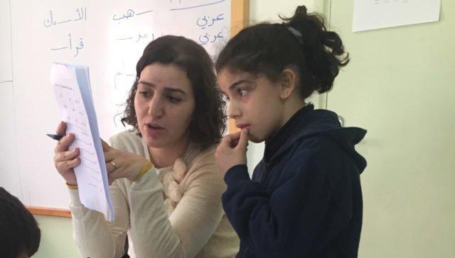 Lärare hjälper elev att läsa