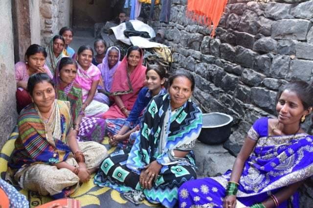 Kvinnor sitter i ett gathörn och diskuterar och har utbildning