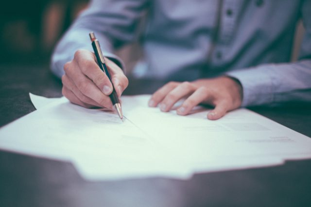 Man som skriver på papper