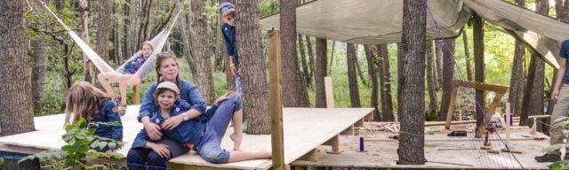Scouter bygger en plattform bland träden i skogen