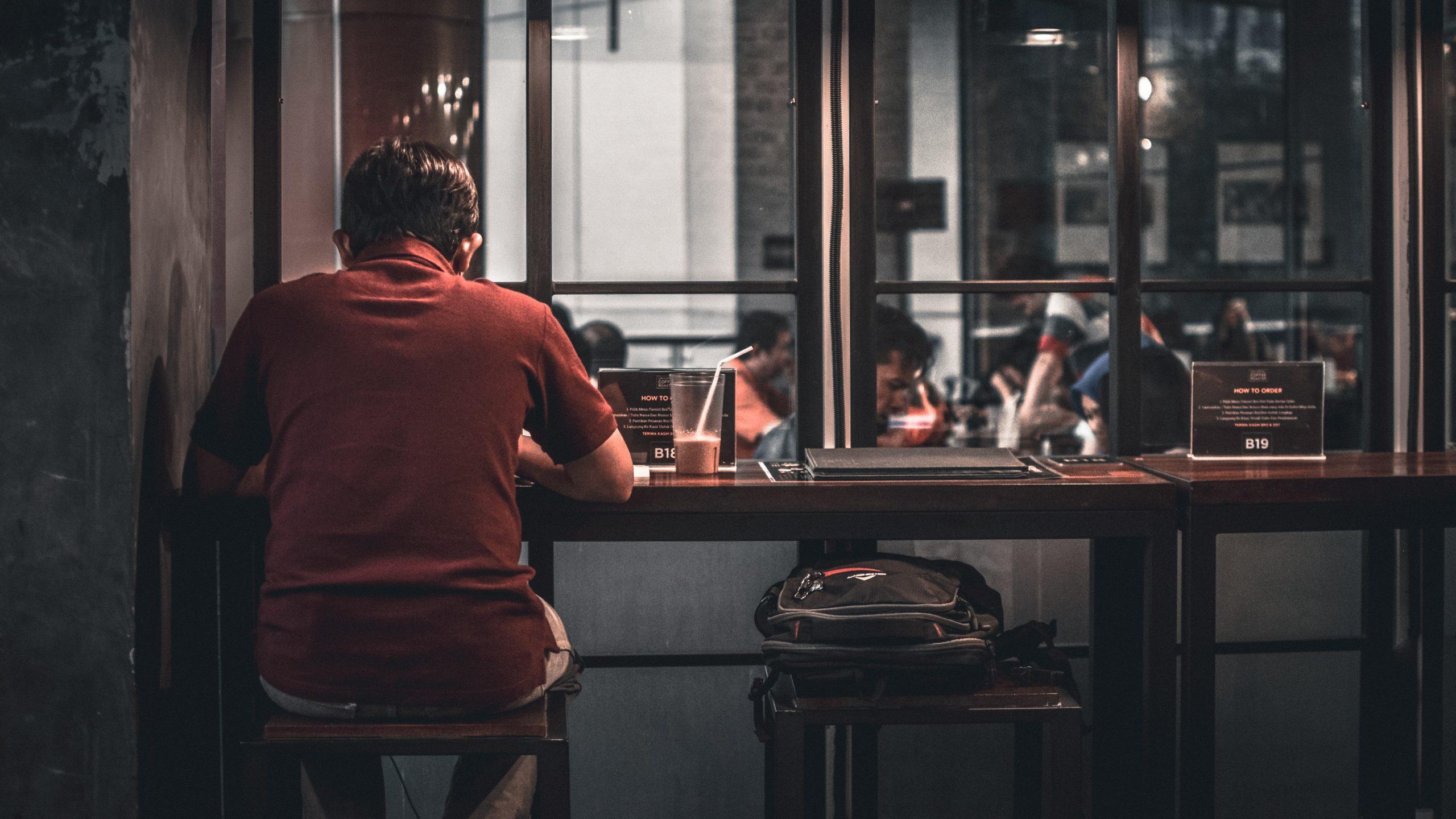 En ensam man vid ett fönster på ett café
