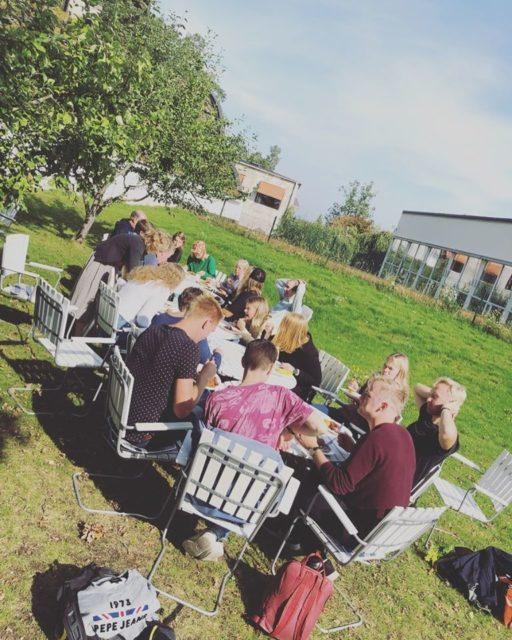 Ungdomsledare äter mat utomhus, sommar.