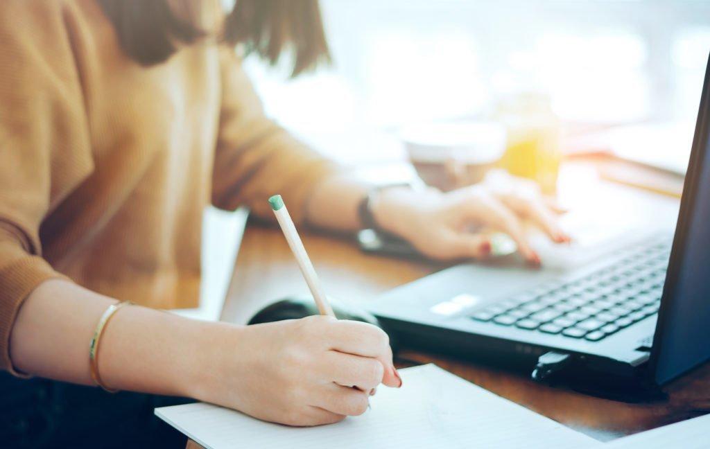 Kvinna med laptop, penna och papper