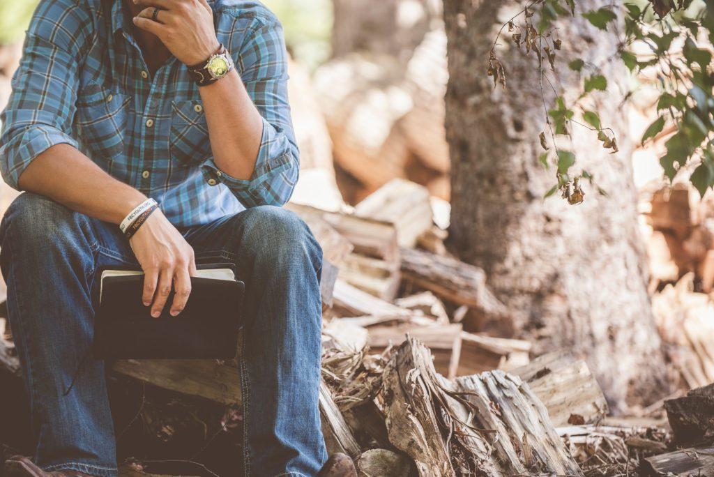 Man som ber med bibel i handen