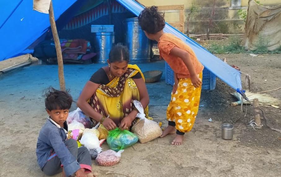 Kvinna sitter med barn omkring sig i Pune, Indien.
