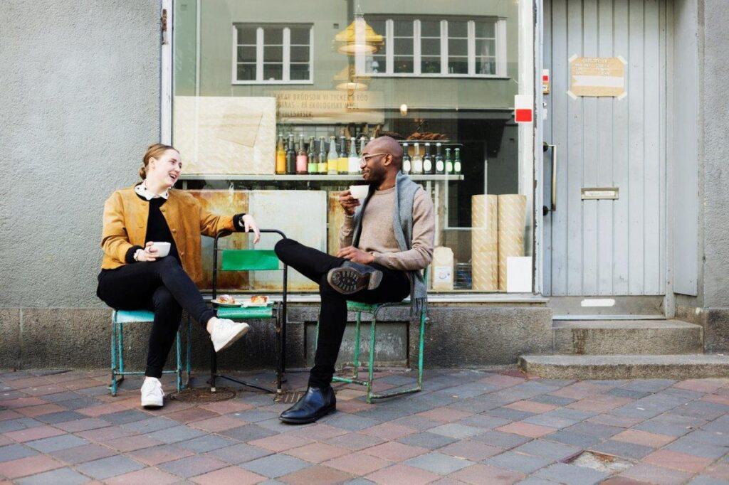 Kvinna och man som dricker kaffe utanför ett kafé