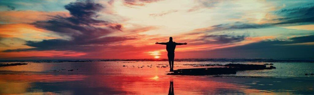 Motljus och siluette av en person som står vid havet i solnedgången