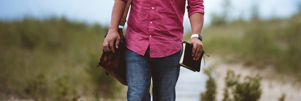 En man som går utomhus med en bibel i handen