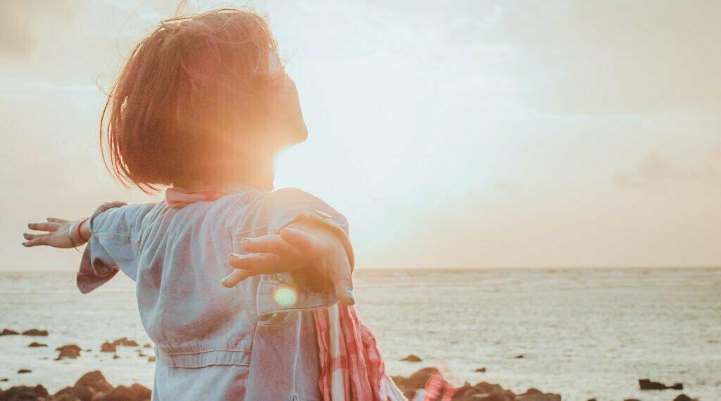 Kvinna som står med utsträckta händer i soluppgången vid en strand.