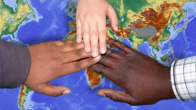 Händer ovanpå en världskarta