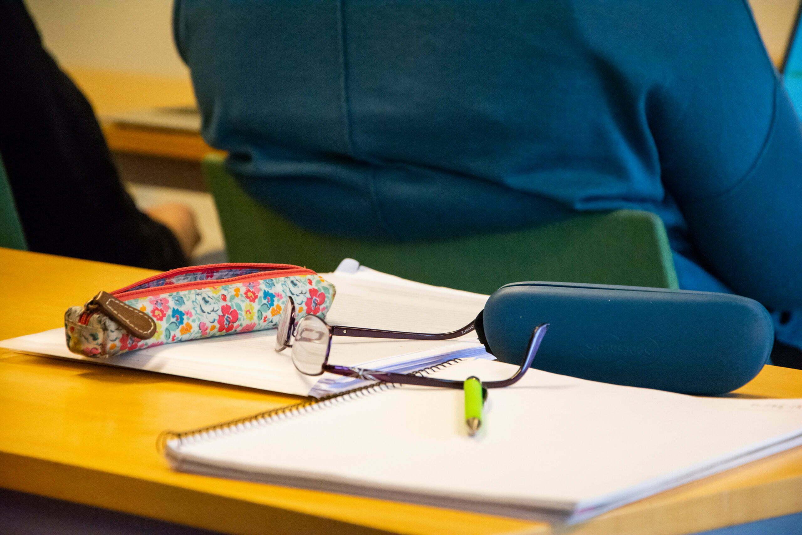 Penna, papper och glasögon på ett bord i en lektionssal.